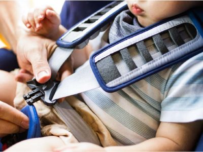 father-fastening-seat-belt-for-his-son-sitting-in