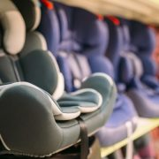 Child car seats variety on shelf in store, nobody