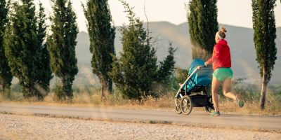 Mother with baby stroller running at sunset landscape